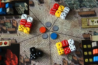 Rynek miejski - Kości pracowników gracza niebieskiego, pomarańczowego oraz neutralnego wraz z czarnymi kośmi z kart zagrożeń
